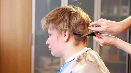 kuaför : the hairdresser does a hairstyle to the client - young man