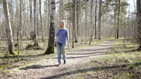 goes : The happy woman goes on a footpath in park in  early spring Stock Footage