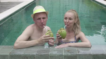 caráter : Loving couple the man and the woman have a rest in the pool in the tropical resort also drink cocktail from coconut Stock Footage