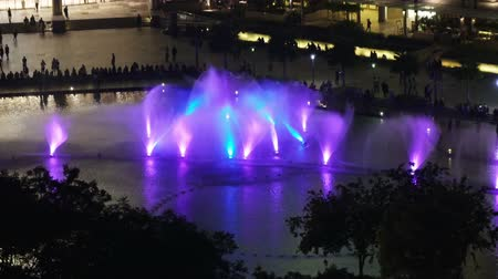 ikrek : KUALA LUMPUR, MALAYSIA- OCTOBER 12, 2016 : The fountains lit with color light at Petronas twin towers in night Kuala Lumpur Malaysia