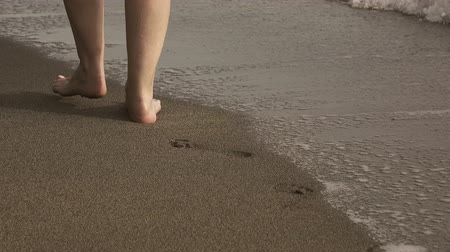 close up female legs go in a strip of a sea surf on the sandy tropical beach early in the morning