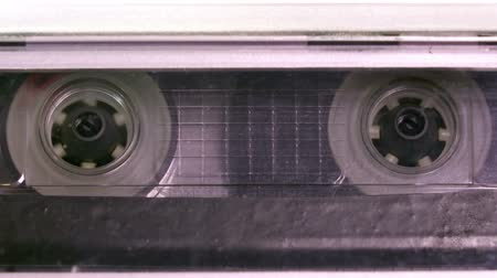 casette : Audio cassette tape in use sound recording in the tape recorder. Vintage music cassette with a blank white label, playing back in the player