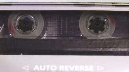 аналог : Audio cassette tape in use sound recording in the tape recorder. Vintage music cassette with a blank white label, playing back in the player