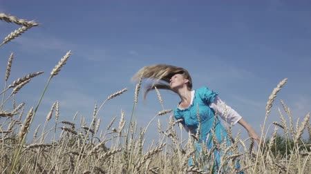 hair growth : happy young slender woman with a long fair hair in a blue dress rotates in the field of ripe wheat in summer sunny day.Slow motion