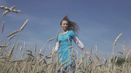 ekili : happy young slender woman with a long fair hair in a blue dress rotates in the field of ripe wheat in summer sunny day.Slow motion