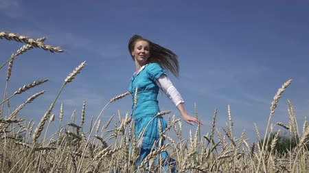 árpa : happy young slender woman with a long fair hair in a blue dress rotates in the field of ripe wheat in summer sunny day.Slow motion