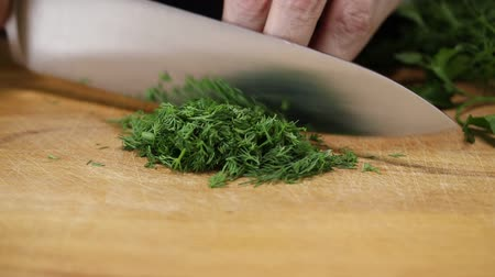 kapor : Woman thinly cuts dill with a kitchen knife on a wooden board, close-up