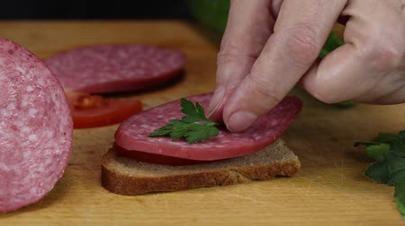 fumado : Woman makes a sandwich from a slice of gray bread, a slice of tomato, smoked sausage and a leaf of greens, close-up