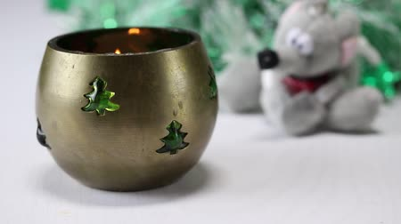castiçal : The fire burns in a metal decorative Christmas candlestick against a background of an artificial Christmas tree and a soft toy in the form of a rat