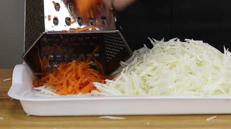 shred : A man rubs a carrot on a metal vegetable grate for subsequent salting, close-up