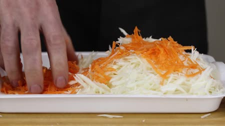 pickling : A man pours thinly shabby carrots into thinly sliced cabbage, close-up