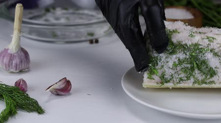 kapor : The chef soaks in salt, garlic and chopped dill a large piece of pork fat and puts it on a white plate