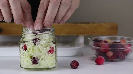 pickling : Woman puts sliced cabbage and cranberries in a glass jar, close-up