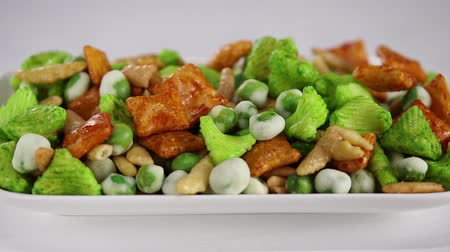 ervilhas : Female hands put a large tray with Japanese sharp snacks with peas and wasabi on a white surface, side view, close-up