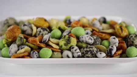 ervilhas : Female hands put a large tray with Japanese sharp snacks with peanuts, peas and wasabi left-top on a white surface, side view, close-up