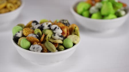 ervilhas : Japanese hot snacks with peanuts, peas and wasabi lie in a white bowl in the foreground, in the background Japanese hot snacks with peanuts, peas and wasabi are poured into an empty bowl, side view, close-up