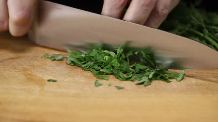 shred : Woman thinly slices a bunch of parsley with a large kitchen knife on a cutting board Stock Footage