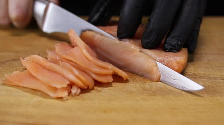 filet : Chef cuts salmon into thin slices, close-up