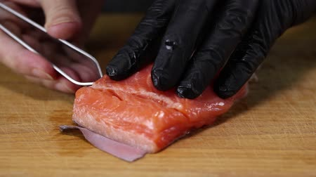 truta : Chef pulls tweezers bones from trout fillet, close-up