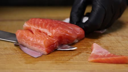 truta : The chef is using a knife to separate the trout fillet from the skin, closeup