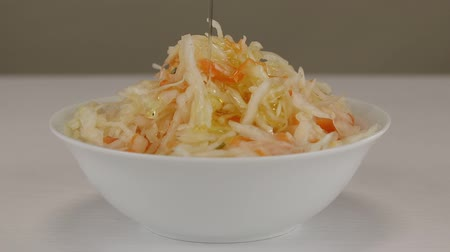 pickling : Olive oil is added to a white bowl with fermented cabbage and carrots, close-up