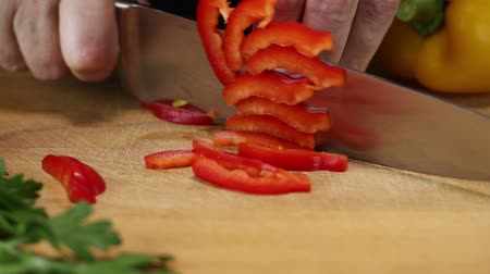 bolgár : Woman slices red bell pepper into slices with a large kitchen knife on a cutting board