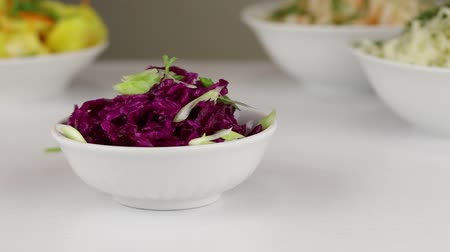 pickling : Chopped green onions are added to a white bowl with fermented red cabbage, close-up Stock Footage