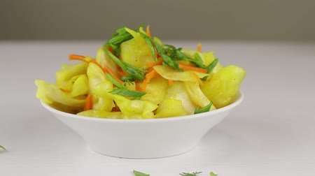 kari : Chopped green onions are added to a white bowl with fermented cabbage and carrots with curry seasoning, close-up Dostupné videozáznamy