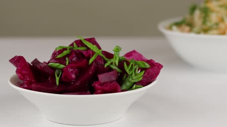 pickled : Green chopped onions are added to a white bowl with fermented cabbage and beets, close-up