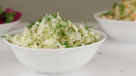 kapor : Fresh greens are added to a white bowl with fermented cabbage with dill, close-up Stock mozgókép