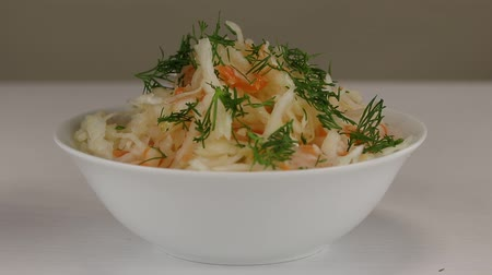 kapor : Fresh chopped dill is added to a white bowl with fermented cabbage and carrots, close-up