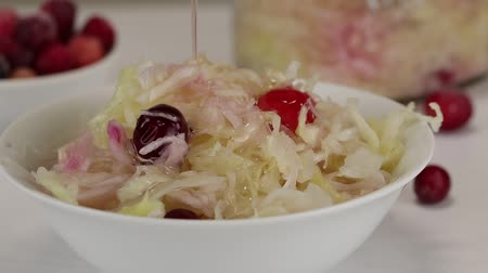pickling : Olive oil is added to a plate with fermented cabbage with cranberries, close-up Stock Footage
