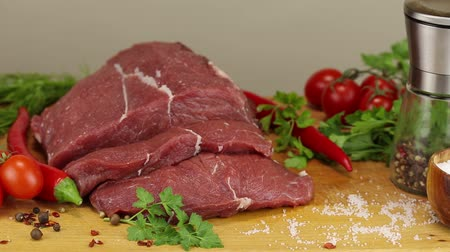 dana eti : Beef steaks and vegetables on a wooden board on a gray background, close-up