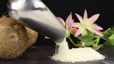 心のこもった : A female hand spills grated coconut shavings from a metal scoop onto a black surface, close-up 動画素材