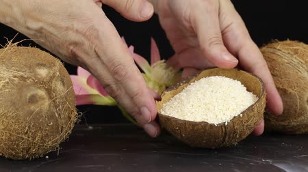 ralado : Female hands lay the shell with grated coconut on a black surface, close-up
