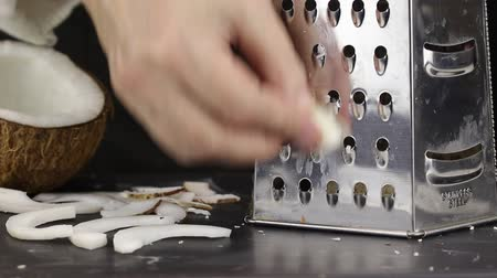 心のこもった : A female hand rubs a slice of coconut on a metal grater to obtain chopped coconut flakes, close-up 動画素材