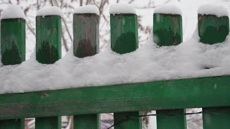 mentiras : Snow lies on a green wooden fence Vídeos