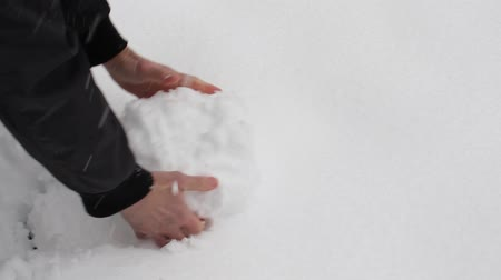 srážky : A man rolls a ball of fallen snow