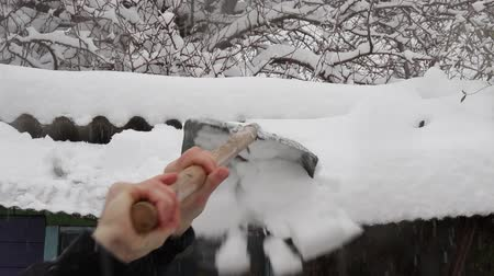 srážky : A man cleans a roof with a shovel from snow