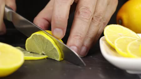 szorítás : Female hand cuts half a lemon into half rings Stock mozgókép