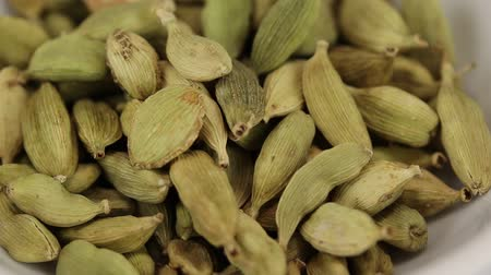 kardámom : Cardamom fruits fall in a glass transparent bowl, close-up Stock mozgókép