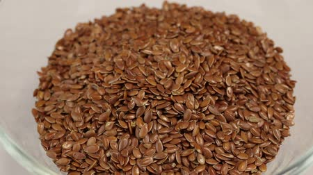 surový : Flax seeds fall in a glass transparent bowl, close-up Dostupné videozáznamy