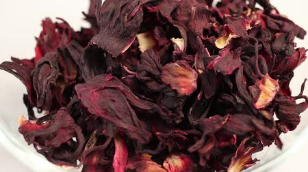 hibiscus : Large leaves of Hibiscus tea fall in a transparent glass bowl, close-up Stock Footage