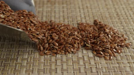 rode draad : Flax seeds falls out of a metal scoop