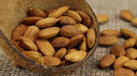 珍味 : Almonds lie in two empty coconut shells and on a gray wicker surface