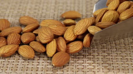 珍味 : Almond nuts fall out of a metal scoop onto a gray wicker surface, close-up