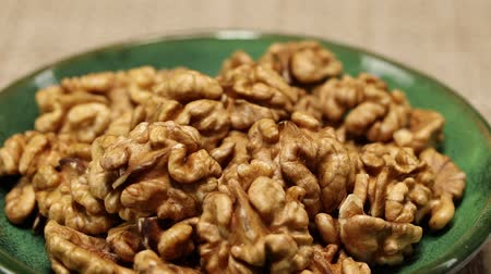 nozes : A green plate with walnuts is placed on a gray wicker surface, close-up Stock Footage