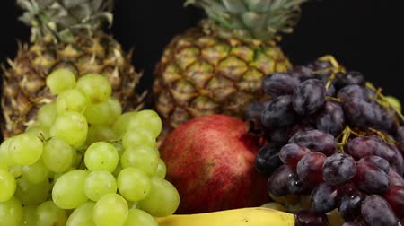 banan : Two pineapples, grapes, pomegranate and bananas lie on a silver tray, close-up Wideo