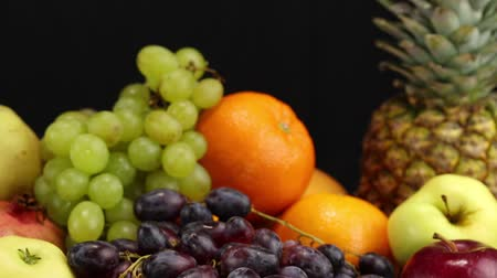 banan : A lot of different fruits lies on a gray surface on a black background, close-up Wideo