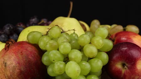roma : Red apples, green grapes and large pomegranate rotate counterclockwise, side view